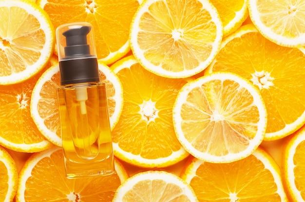 髪用オイルが入った無印のガラス容器の上面図。ディスペンサー付きの透明なボトル。背景にオレンジとレモンのジューシーなスライス。広告、コピースペース。美容と美容のコンセプト。