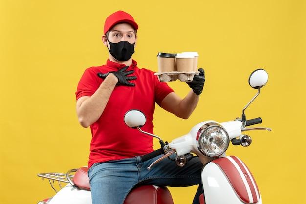 スクーターに座っている医療用マスクの制服と帽子の手袋を着用している不確かな配達人の上面図は、自分自身を指している注文を示しています