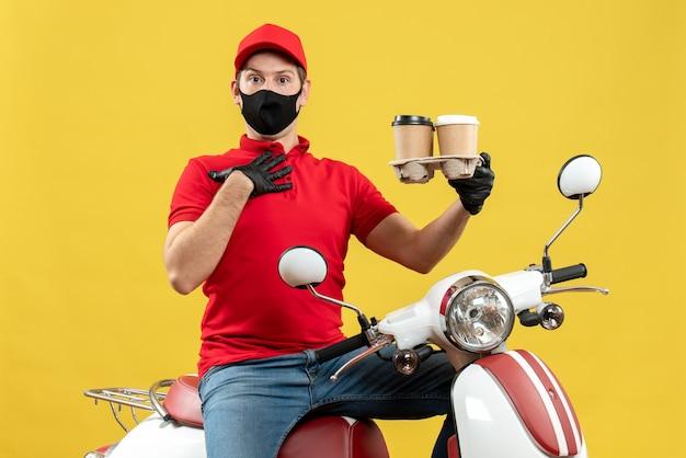 注文を示すスクーターに座っている医療用マスクで制服と帽子の手袋を着用している不確かな配達人の上面図