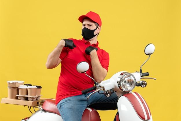 黄色の壁のスクーターに座って注文を配信医療マスクで赤いブラウスと帽子の手袋を身に着けている不確かな不確かな若い大人の上面図