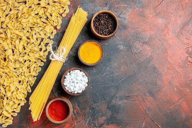 검은 배경에 다양한 형태와 다른 향신료의 생 쌀된 파스타의 상위 뷰