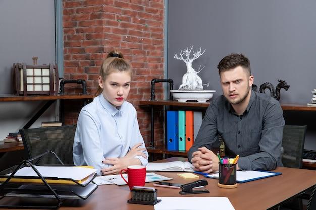 사무실에서 카메라를 위해 포즈를 취한 테이블에 앉아 있는 불행하고 의욕이 없는 사무실 팀의 상위 뷰