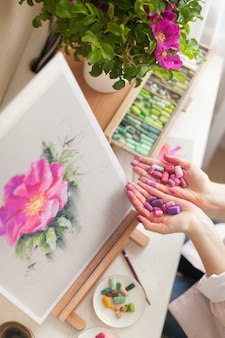 Вид сверху неопознанного молодого художника, держащего сухую пастель в розово-фиолетовых тонах, при создании эскиза ярко-розового цветка шиповника на рабочем столе рядом с мелками в зеленых тонах и букетом шиповника в вазе