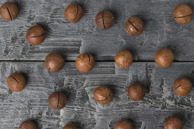 木製のテーブルの上の皮をむいていないマカダミアナッツの上面図。スーパーフード。