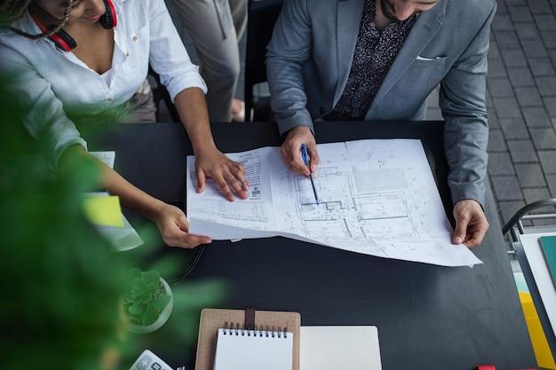 인식할 수 없는 건축가가 사무실 책상에 앉아 작업하는 최고의 전망, 협력 개념.