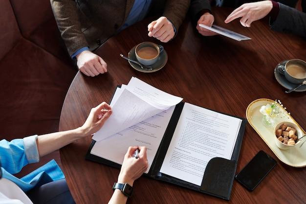 Вид сверху неузнаваемой бизнес-леди, подписывающей контракт после переговоров с деловыми партнерами в кафе