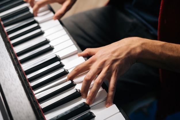 홈 스튜디오에서 신디사이저에서 연주하는 알아볼 수 없는 음악가 남자의 상위 뷰