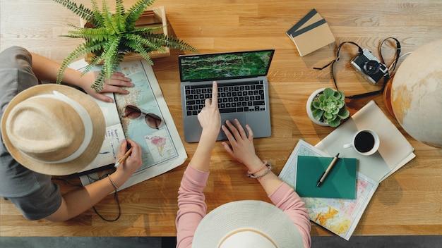 휴가 여행 휴가를 계획하는 노트북과 지도가 있는 알아볼 수 없는 젊은 부부의 상위 뷰