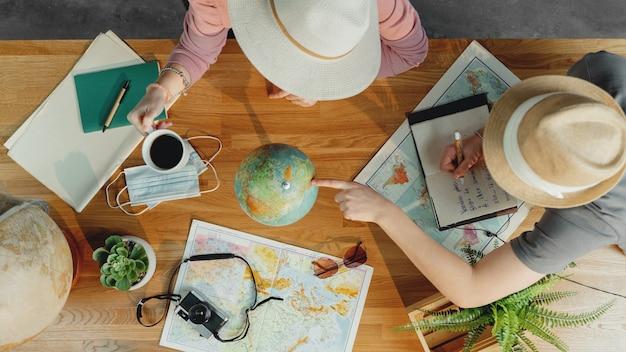 Вид сверху неузнаваемой молодой пары с картами, планирующими поездку в отпуск, отпуск на рабочий стол