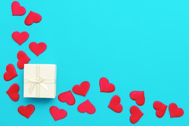 Взгляд сверху предпосылки валентинки сделанной из белой подарочной коробки и красных текстильных сердец. любовь и концепция дня святого валентина. фото высокого качества