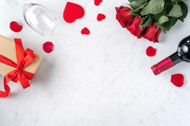 バラとワイン、特別な休日のデートの食事のためのお祝いのデザインコンセプトとバレンタインデーのギフトの上面図。