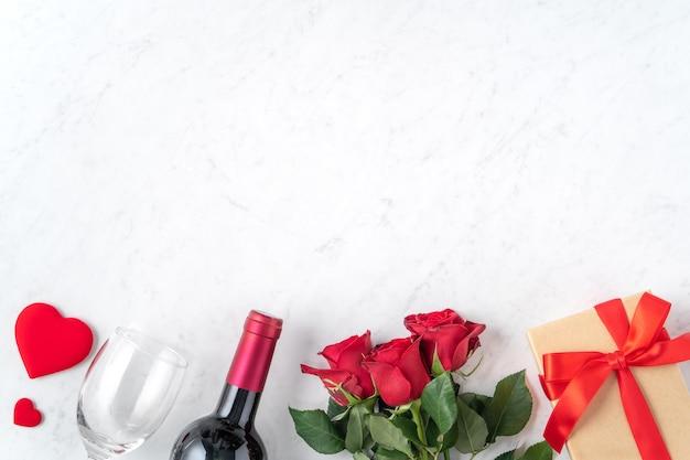 Вид сверху на подарок на день святого валентина с розой и вином, праздничная концепция дизайна для особого праздничного ужина.