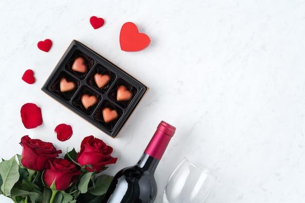 Вид сверху на шоколад на день святого валентина с розой и вином