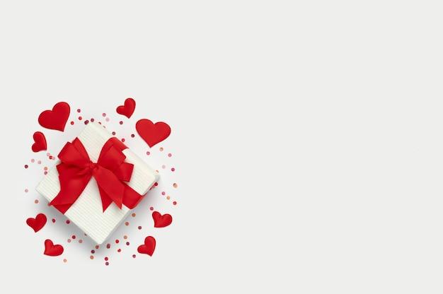 コピースペースとバレンタインデーのコンセプトの上面図。白い背景に小さなハートと紙吹雪がたくさんあるギフトボックス。