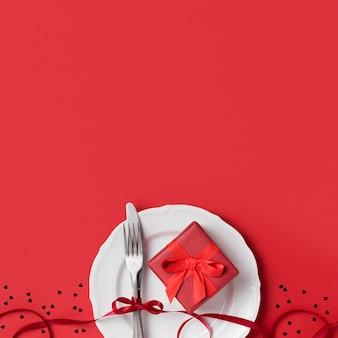 Вид сверху подарка на день святого валентина на тарелке с лентой и столовыми приборами