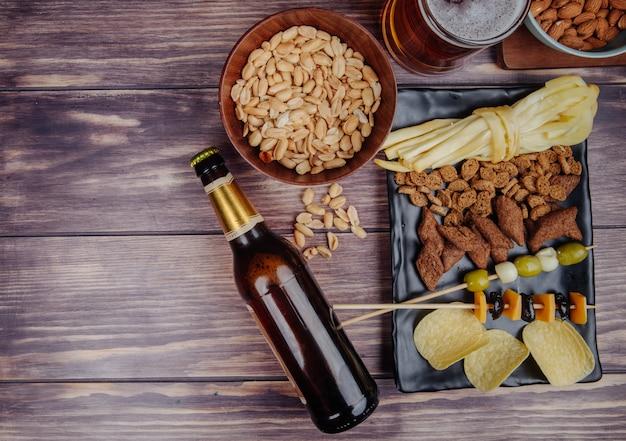 Вид сверху разнообразных закусок к пиву с бутылкой пива на деревенском с копией пространства