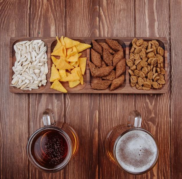 Вид сверху разнообразных соленых пивных закусок из семян подсолнечника кукурузные шишки и хлебные крекеры на деревянной тарелке с двумя кружками пива на деревенском дереве
