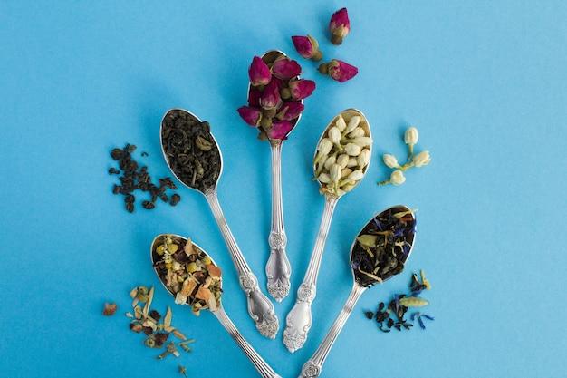 Вид сверху разновидностей чая в серебряных ложках на синем