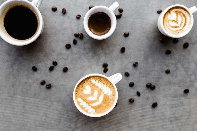 Вид сверху различных кофейных чашек и кофейных зерен