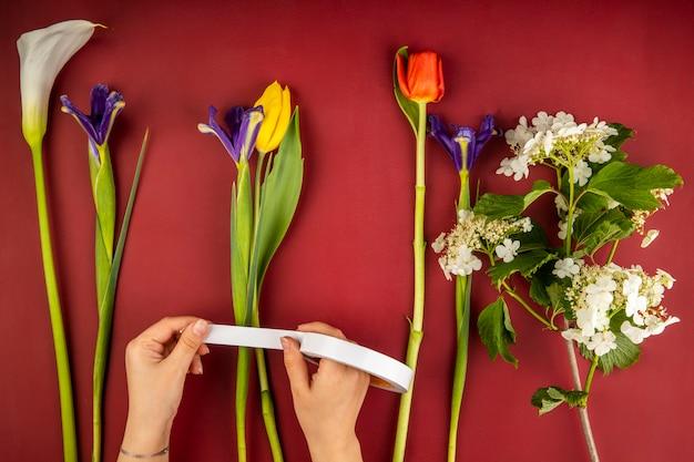 赤と黄色の色のチューリップ、オランダカイウユリ、濃い紫色のアイリスの花、赤いテーブルに咲くガマズミ属の木の花束のさまざまな花のトップビュー