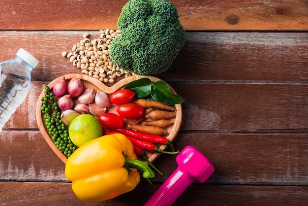 ハートプレートとスポーツシューズのさまざまな新鮮な有機果物と野菜の上面図