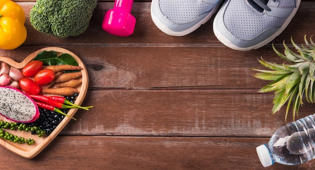 Вид сверху различных свежих органических фруктов и овощей в сердечной тарелке и спортивной обуви