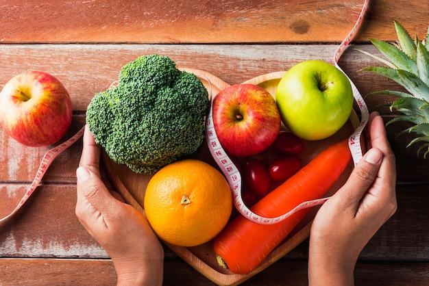 ハートプレートと女性が手を使用してさまざまな新鮮な有機果物と野菜の上面図