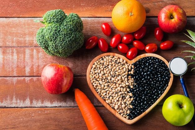 Вид сверху различных свежих органических фруктов и овощей в сердечной тарелке