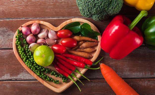 ハートプレートのさまざまな新鮮な有機果物と野菜の上面図