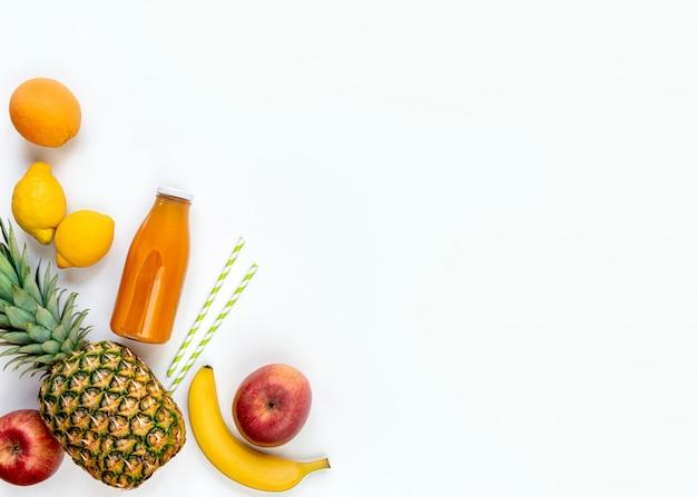 다양 한 과일과 흰색 배경에 갓 압착 된 종합 비타민 주스의 병의 상위 뷰. 공간을 복사하십시오. 평평하다.