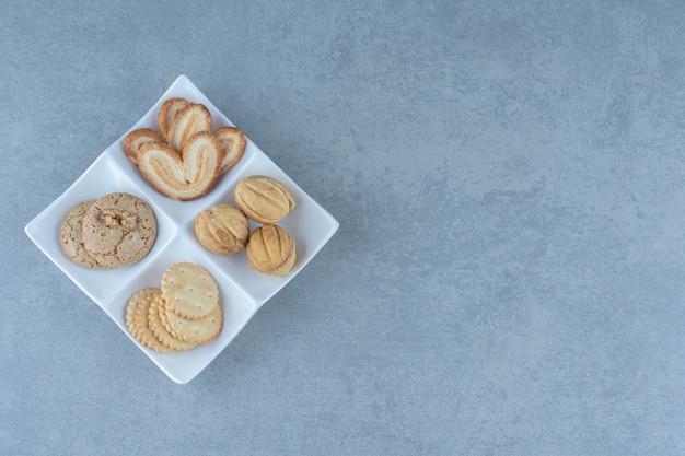 하얀 접시에 있는 다양한 종류의 쿠키의 상위 뷰.