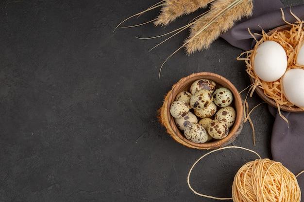 Вид сверху на различные органические яйца в коричневом полотенце с шипами и веревкой слева на темном фоне