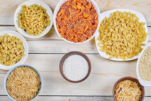 Вид сверху различных сырых макарон на белые и деревянные миски с мукой.