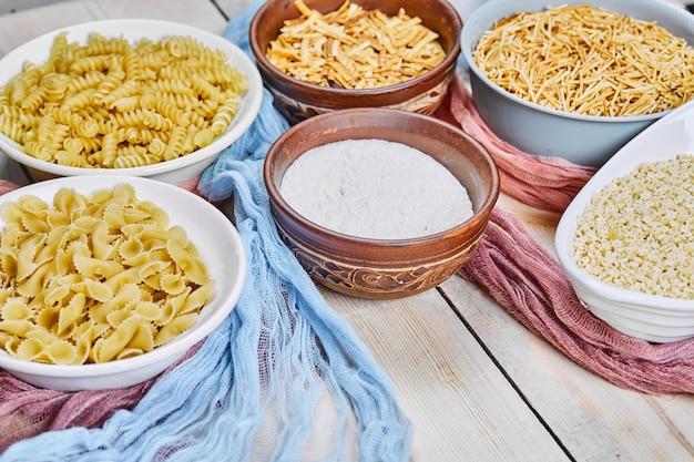 Вид сверху различных сырых макаронных изделий и миски муки на деревянном столе с голубой и розовой скатертью.