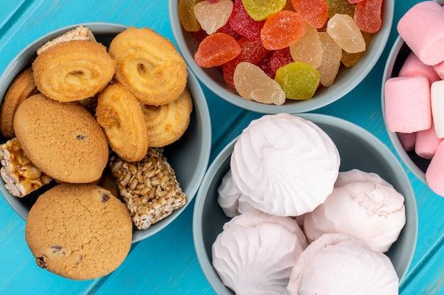 Вид сверху различные сладости печенье красочные мармеладные конфеты и зефир белый зефир в мисках на синем
