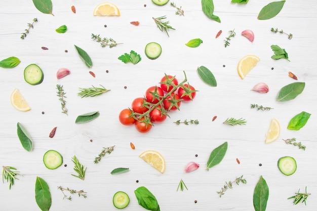 Вид сверху различных видов листьев ароматных трав и нарезанных овощей на деревянной поверхности