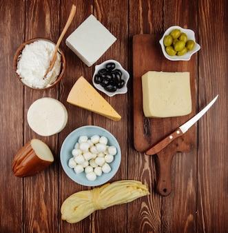 キッチンナイフで木製のまな板にチーズと素朴なテーブルのボウルにカッテージチーズとピクルスオリーブのさまざまな種類のトップビュー