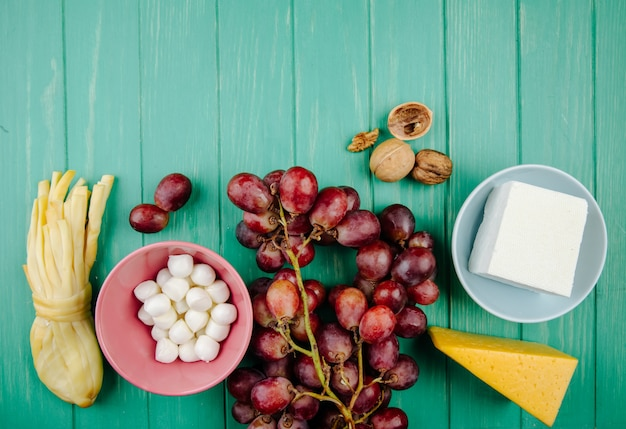 Взгляд сверху различных типов сыра с свежим виноградом на древесной зелени с космосом экземпляра