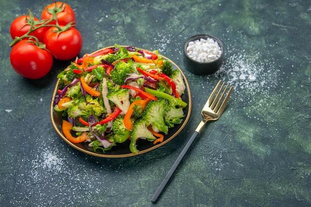 暗い背景に茎を持つさまざまな野菜とフォークトマトとプレートのビーガンサラダの上面図