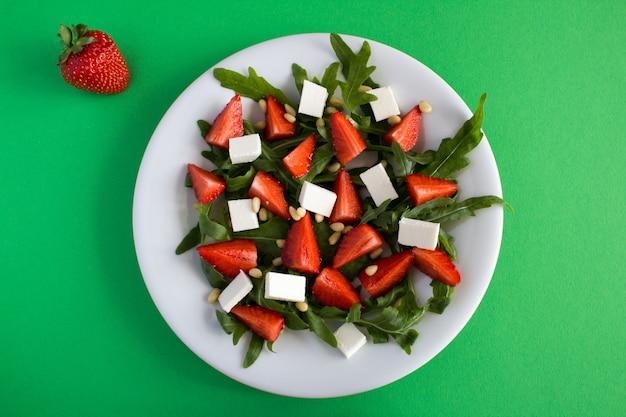 緑の白いプレートにイチゴ、ルッコラ、ソフトチーズ、松の実を添えたベジタリアンサラダの上面図