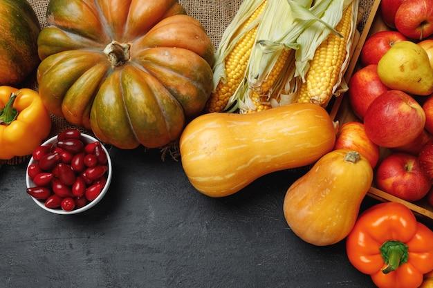 Вид сверху овощной композиции с тыквами и яблоками на черном фоне