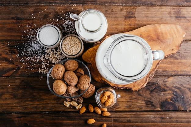 木の背景に野菜ミルク、アーモンドミルク、クルミミルク、ライスミルク、ココナッツミルクの上面図