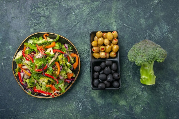 暗い背景の上のプレートの緑と黒のオリーブブロッコリーの野菜サラダの上面図