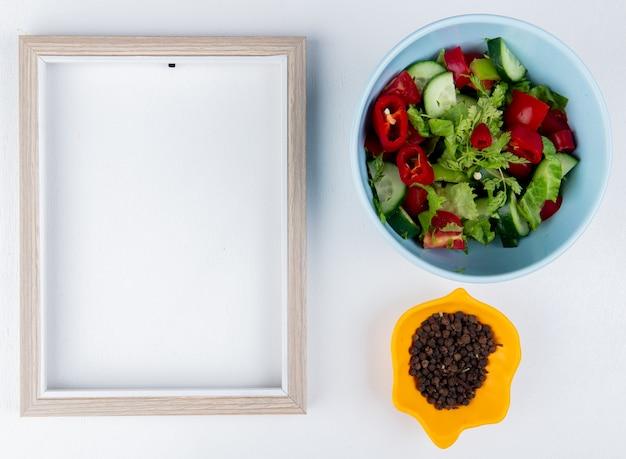 Вид сверху овощной салат в миску и семена черного перца в миску с рамкой на белой поверхности с копией пространства