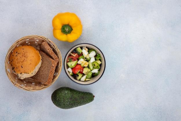白い表面に黄色いピーマンとアボカドのパンのバスケットとボウルにキュウリトマトコショウを含む野菜サラダのトップビュー