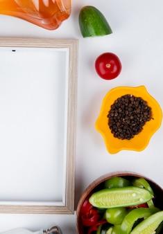 Вид сверху овощного салата с черным перцем, нарезанным огурцом помидором, растопленным сливочным маслом, солью и рамкой на белой поверхности