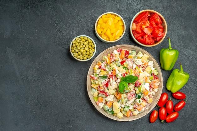 灰色の背景の左側にテキスト用の空きスペースがある側にさまざまな野菜と野菜サラダの上面図