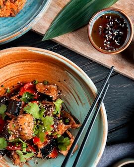 Вид сверху овощного салата с жареными баклажанами, помидорами, травами и кунжутом в миске с соевым соусом по дереву
