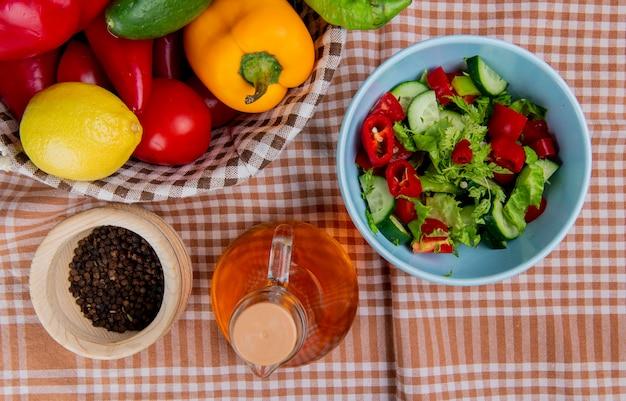 Вид сверху овощного салата с лимонным огурцом и томатным перцем в корзине с семенами черного перца и растопленным маслом на поверхности ткани пледа