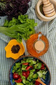 Вид сверху овощного салата с салатом-базиликом, черным перцем, чесночной дробилкой, растопленным сливочным маслом на клетчатой ткани